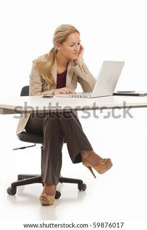 Young business girl sitting at desk with laptop - stock photo