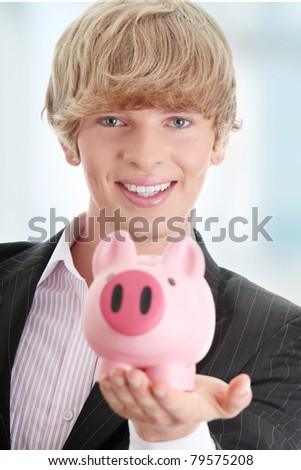 Young business holding piggy bank