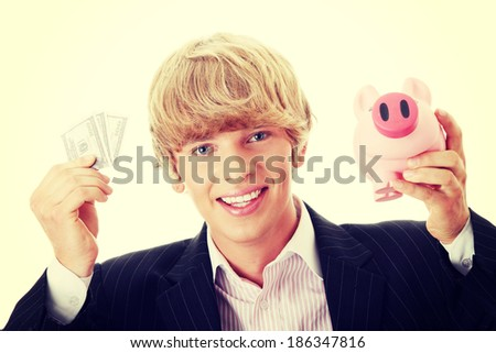 Young business holding piggy bank and dollars - stock photo