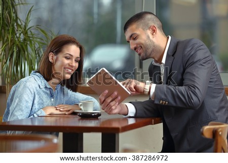 Young business man and women drinking caffe and smiling while using tablet - stock photo