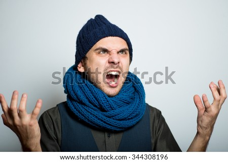 young business man angry shouts winter style clothes, studio shot isolated on the gray background