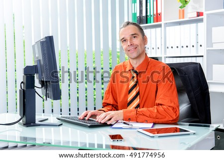 young business man at his desk looking friendly in to the camera