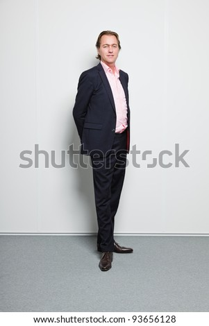 Young business man blond hair wearing blue suit and pink shirt isolated on white background. - stock photo