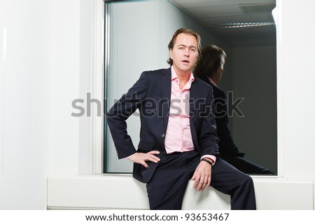 Young business man blond hair wearing blue suit and pink shirt standing in front of window. - stock photo