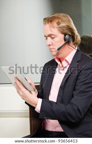Young business man blond hair with headset and tablet wearing blue suit and pink shirt in front of window. - stock photo