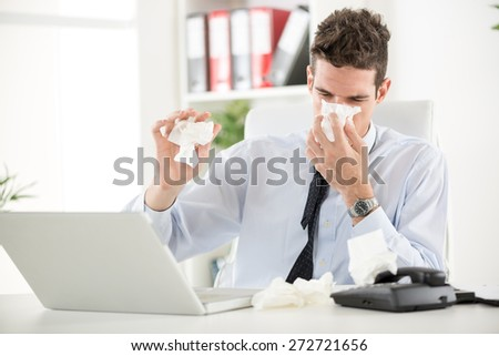 Young business man blows his nose while working at his laptop in the office. - stock photo