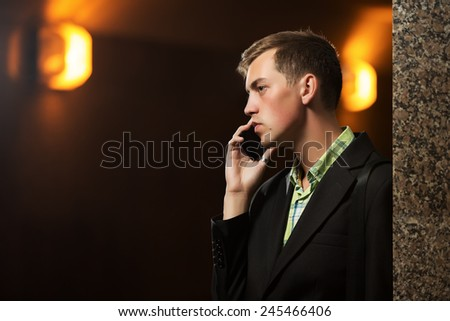 Young business man calling on mobile phone at the wall - stock photo