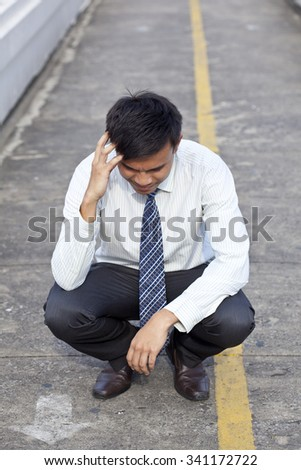 Young business man crying abandoned lost in depression sitting on ground street - stock photo