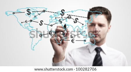 Young business man drawing a global network with Dollar Signs on world map.  The metaphor of international communication around the world. On a gray background. - stock photo