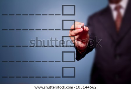 Young business man drawing a tick on a glass window in an office. Man choosing - stock photo