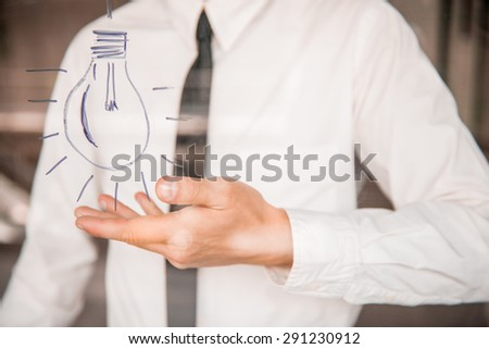 Young business man drawing an idea on glass window at office. Close-up. - stock photo