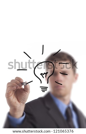 Young business man draws a lightbulb. - stock photo
