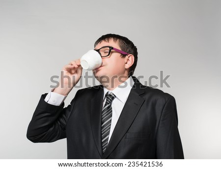 Young Business Man Drinking a Cup of Coffee or Tea - stock photo
