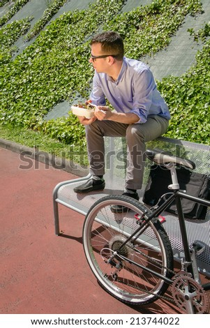 Young business man eating a salad at lunch break sitting on a bench outdoors - stock photo