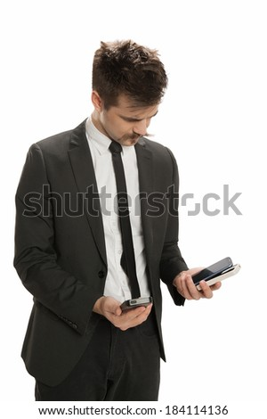 Young business man examines several cell phones - stock photo