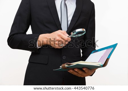 Young business man hold a book and magnifying glass - stock photo