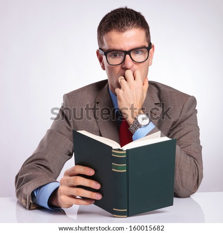 young business man holding a book and reading it frightened, while biting his nails. on a gray background