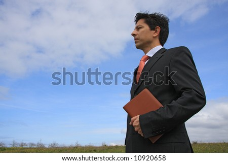 Young business man holding a executive notebook ready to work on the nature - stock photo