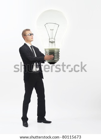 Young business man holding a huge lightbulb - stock photo
