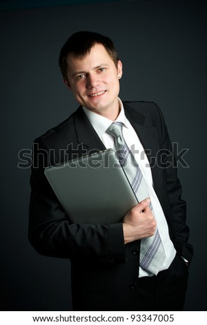 Young business man holding a laptop
