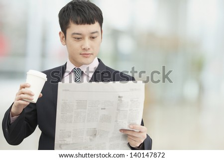 Young business man holding coffee cup and reading newspaper