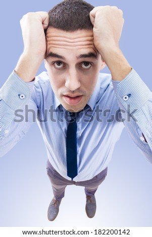 Young business man holding his head frowning with worry, taken from above - stock photo