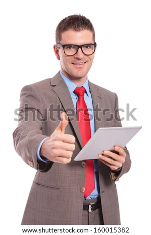 young business man holding his tablet and showing the thumb up gesture to the camera while smiling. on a white background