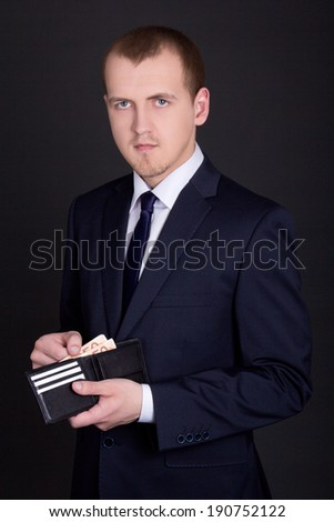 young business man holding leather purse with euro banknotes - stock photo
