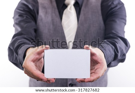 Young business man holding white paper card on a white background - stock photo