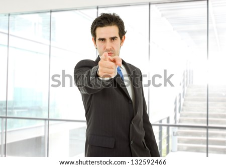young business man in a suit pointing with his finger at the office - stock photo