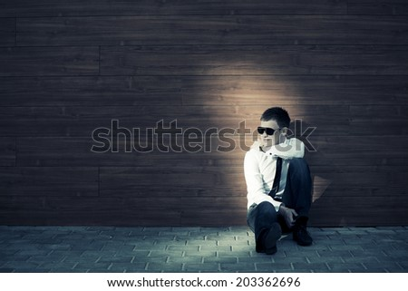 Young business man in depression sitting at the wall  - stock photo