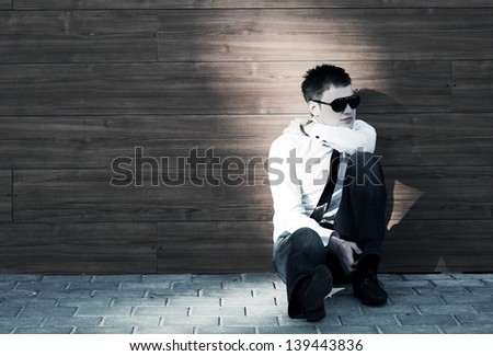 Young business man in depression sitting on the sidewalk - stock photo