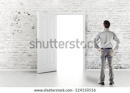 young business man in front of an open door in a vintage white brick wall - stock photo