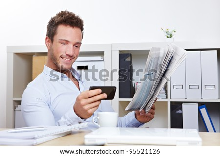 Young business man in office looking for job with smartphone and newspaper - stock photo