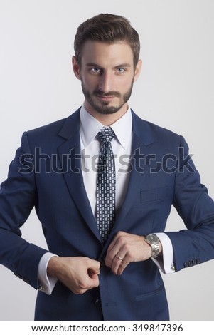 Young Business Man in Suit Buttoning Jacket