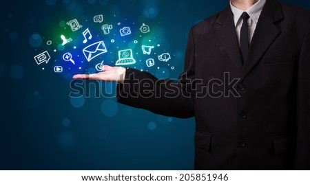 Young business man in suit presenting colorful glowing social media icons - stock photo