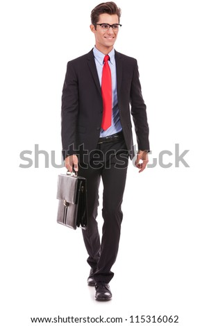 young business man is walking an looking away from the camera while holding a suitcase - stock photo