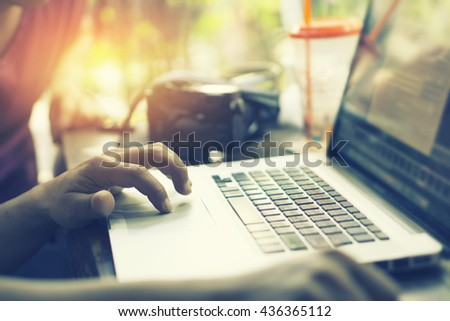 young business man keyboarding on laptop computer with blank copy space screen while sitting in cafe,finger on trackpad of computer,shot touching laptop trackpad,vintage color,selective focus - stock photo