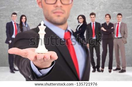 young business man leader of a successful business team holding the white king of chess on the top of his hand - stock photo