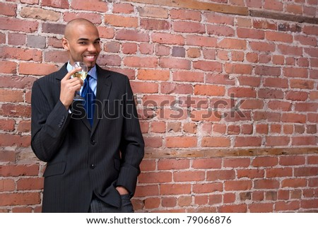 Young business man leaning against the brick wall, drinking wine and smiling. - stock photo