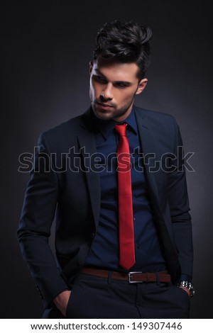 young business man looking away from the camera while holding his hands in his pockets. on a black background