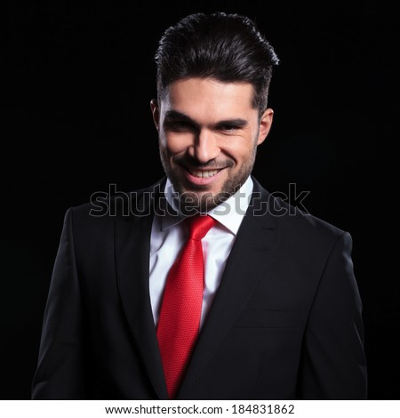 young business man looking into the camera with an evil smile on his face. on a black background - stock photo