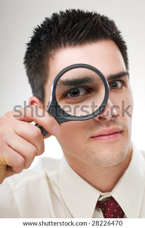 young business man looking through loupe close up - stock photo