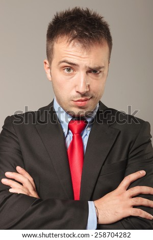Young business man making a funny face over grey backgriund. He is holding his arms crossed while lifting one eyebrow. - stock photo