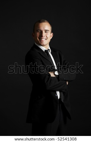 Young business man on black background looking satisfied and smiling - stock photo