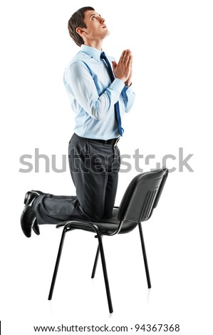 young Business man on his knees praying. Isolated on white
