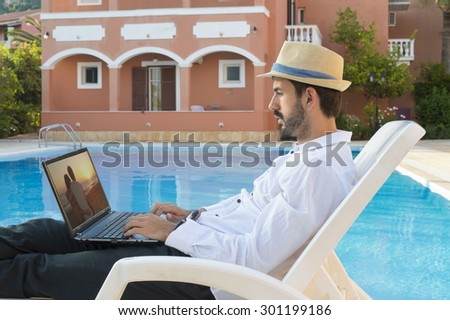 Young business man on pause while working on his lap top by the pool while on vacation  wearing white shirt straw hat - stock photo