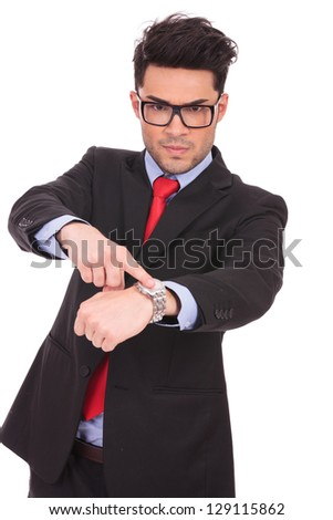 young business man pointing angrily to his watch and looking at the camera, on a white background - stock photo