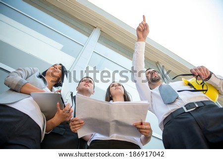 Young business man pointing finger on a construction site - stock photo