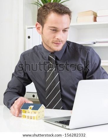 Young business man presenting house mock-up - stock photo